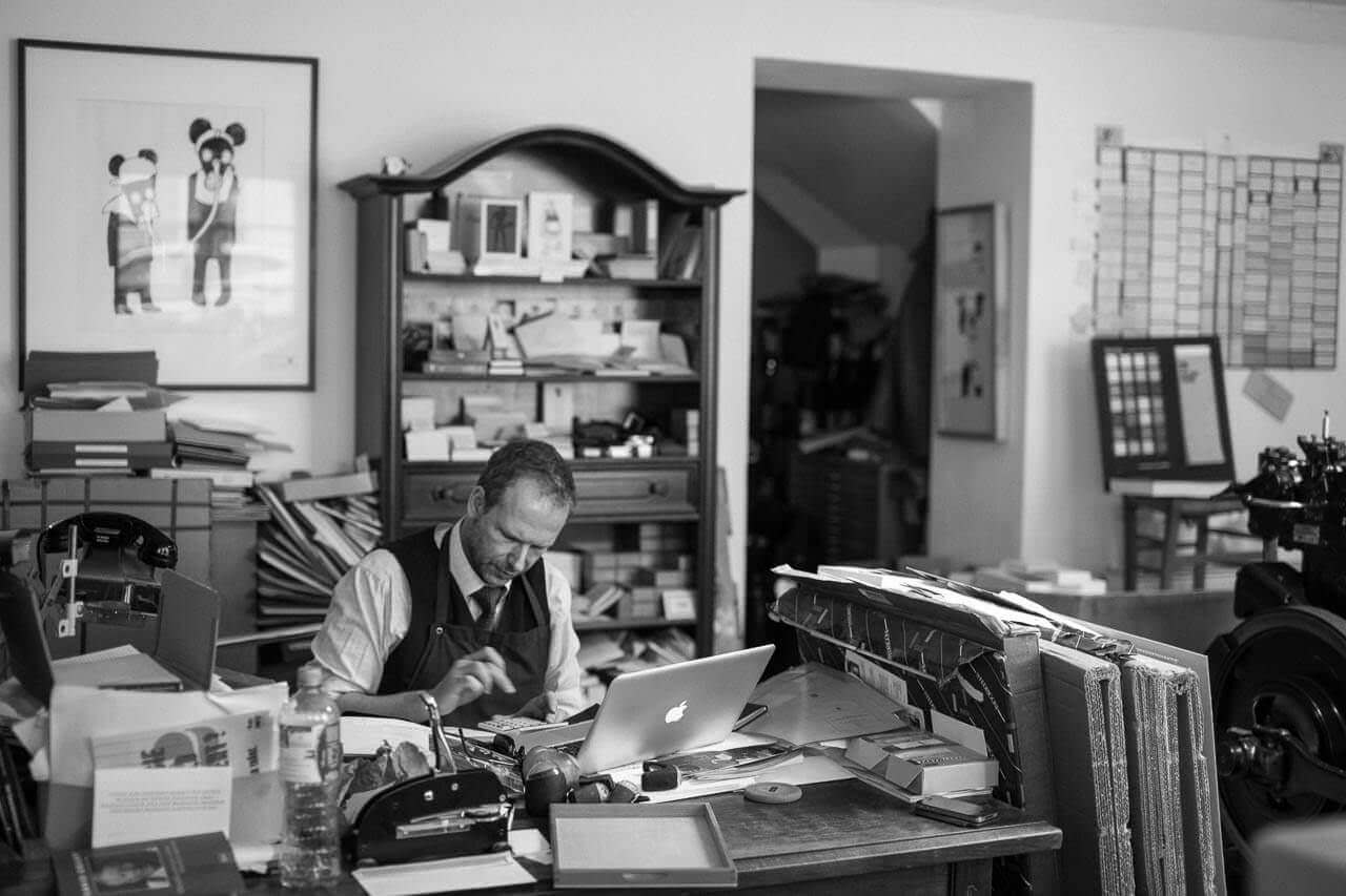 Druckaufträge werden in der Letterpress Druckerei durch Martin Z Schröder an seinem Macbook bearbeitet